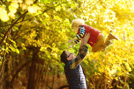 Little boy and his father having fun during stroll in the forest on sunny autumn day. Dad throws child up. Quality family time outdoor. Hiking with kids.