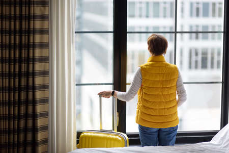 Woman tourist stays in hotel room in New York. Traveler with suitcase looks and admires of amazing view the skyscrapers of Manhattan outside window. Tourism and travel in the USA. Booking apartment