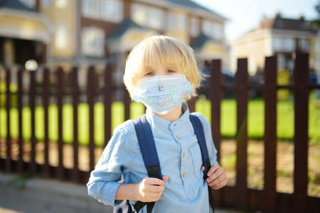 Child in face mask going at reopen school after covid-19 quarantine and lockdown. It is new normal for protection and prevention while outbreak of coronavirus or flu. Kids back to school concept. Stockfoto
