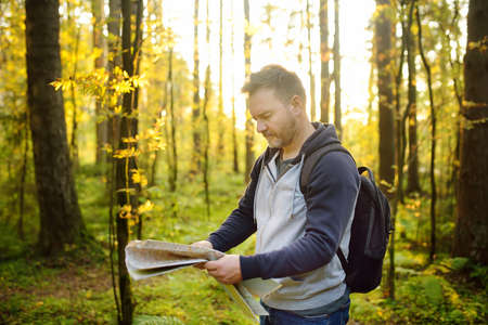 Mature man tourist is hiking. Person looking map during orienteering in sunny autumn forest. Volunteer is searching for people lost in woodland. Outdoors adventure, hike, extreme.