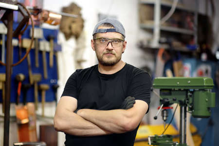Portrait of handsome metalwork craftsman in protective gloves and glasses working in the workshop. Do it yourself. Small local business.