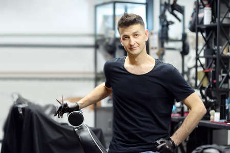 Handsome barber master in salon. Hair artist in man barbershop. Services of professional hair stylist. Fashion haircare for men. Small local business.