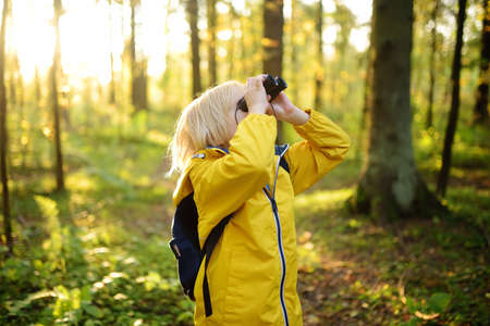 Little boy scout with binoculars during hiking in autumn forest. Child is looking with binoculars. Concepts of adventure, scouting and hiking tourism for kids. Exploring nature Standard-Bild