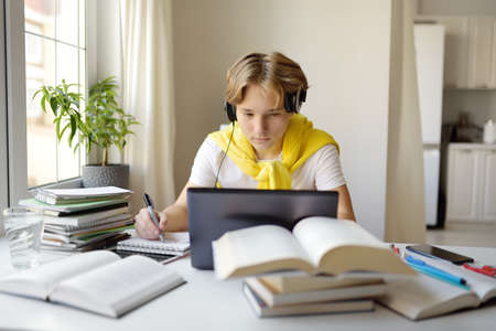 Teenager boy study at home. Online education and distance learning for children. School boy doing his physics homework using gadgets. Lectures and lessons on the internet for high school students