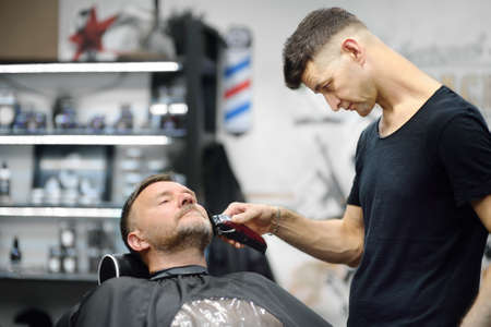 Barber master is shaving of handsome mature bearded man in salon. Hair artist making hairstyle for person in barbershop. Services of professional stylist. Fashion haircare for men Standard-Bild
