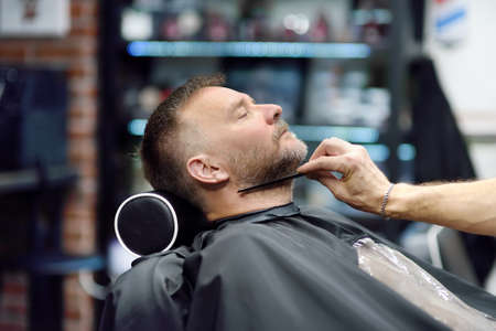 Barber master is shaving of handsome mature bearded man in salon. Hair artist making hairstyle for person in male barbershop. Services of professional stylist. Fashion haircare for men