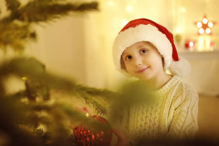 Little boy wearing Santa hat ready for celebrate Christmas. Cute child decorating the Christmas tree with glass toy. Baby hopes of magic and gifts at New Year night. Traditions around winter Holidays