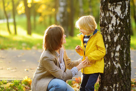 Little boy with his young mother having fun during stroll in the public park at sunny autumn day. Active family time on nature. Hiking with little kids. Leaves rustle. Standard-Bild