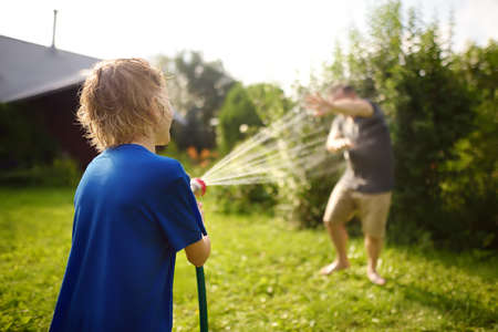Funny little boy with his father playing with garden hose in sunny backyard. Preschooler child having fun with spray of water. Summer outdoors activity for family with kids.