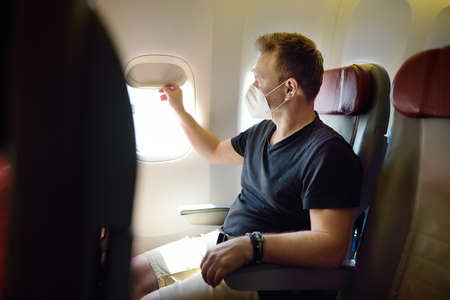 Middle age man in face mask traveling by an airplane. Passenger sitting in aircraft and looking on plane window during flight. Safety and protection of fly transportation while epidemic Standard-Bild