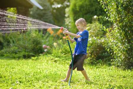 Funny little boy playing with garden hose in sunny backyard. Preschooler child having fun with spray of water. Summer outdoors activity for family with kids. Standard-Bild