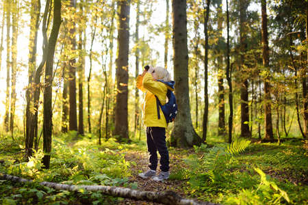 Little boy scout with binoculars during hiking in autumn forest. Child is looking through a binoculars. Concepts of adventure, scouting, hiking tourism and exploring nature for kids.