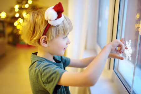 Little excited child getting ready for Christmas. Preschooler boy decorating home - attaching snowflakes to glass, looking on window and waiting Santa Claus. Traditions around New Year and Christmas