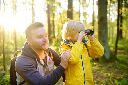 Schoolchild and his father hiking together and exploring nature. Child looking through a binoculars. Little boy with his dad spend quality family time in the sunny summer forest. Fatherhood
