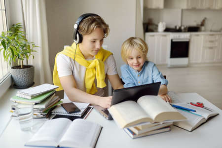 Teenager boy study at home. His younger brother is playing near. Online education and distance learning for children during lockdown. Friendship of siblings with a big age difference. Homeschooling.