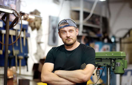 Portrait of handsome metalwork craftsman working in the workshop. Do it yourself. Small local business.
