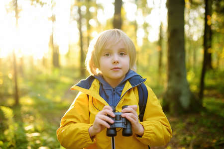 Little boy scout with binoculars during hiking in autumn forest. Concepts of adventure, scouting and hiking tourism for kids. Exploring nature
