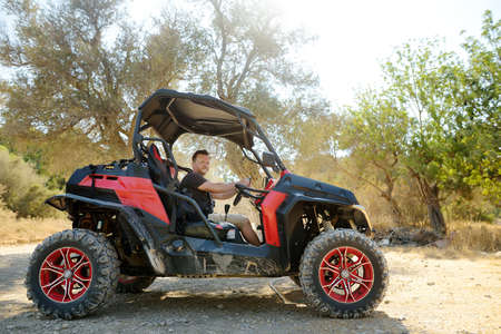 Mature handsome man driving buggy car on sandy hills of Cyprus or Greek in summer. Outdoors adventure, off road extreme trip