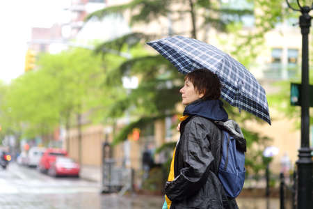 Mature woman tourist with umbrella walking on street of Manhattan in cool rainy spring day. Changeable weather New York. Weather forecast.