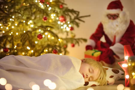Little boy waiting Santa Claus under tree on Christmas Eve. Child is sleeping. Santa Claus brought gifts. Magic at Christmas and New Year night. Traditions of winter Holidays Standard-Bild