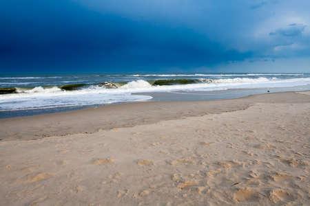 An approaching storm over ocean waves crashing at Assateague Island National Seashore, Maryland