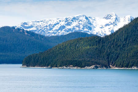 Snow-capped mountains and evergreen trees along the coast of southern Alaska Stock fotó
