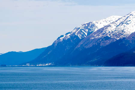 Snow-capped mountains and small town along the coast of southern Alaska