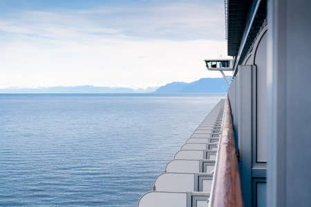 A view of ocean and snow-capped mountains along the coast of Alaska, seen from the balcony of a cruise ship