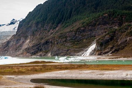 Nugget Falls and small icebergs at the base of Bullard Mountain, next to the Mendenhall Glacier near Juneau, Alaska