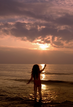 Small child on the beach waving at the sun setting over the sea Stock Photo