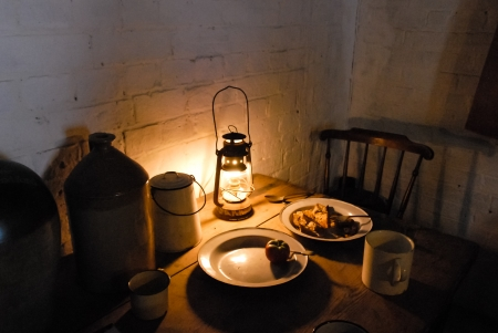 Lamplit Victorian dinner table with lantern, ceramic beer keg and enamel plates and mugs Stock Photo
