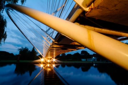 Butterfly river bridge lit from below at dusk with reflection on the water