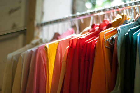 Row of brightly coloured shirts and blouses hanging on a clothes rail and lit by sunlight from a nearby window