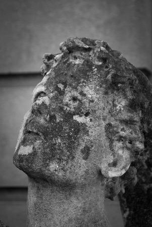 Decaying stone angel looking heavenward