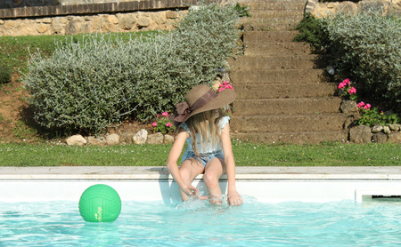 Profile of a girl wearing a brown hat and playing in the swimming pool photo