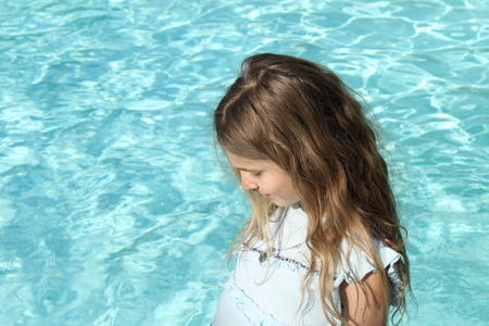 Pretty young girl with blond hair near a pool photo
