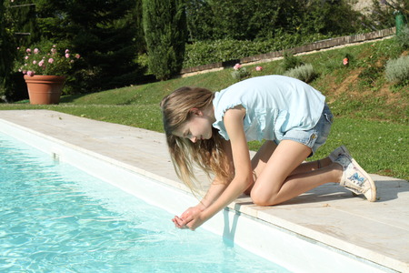 Pretty young girl playing with water at pool s edge photo