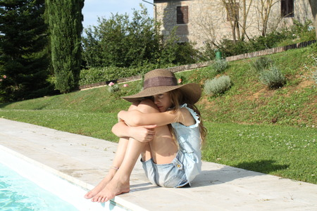 Pretty young girl with arms around knees at the pool s edge photo