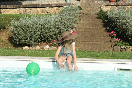 Young girl sitting at pool s edge playing with a green ball photo