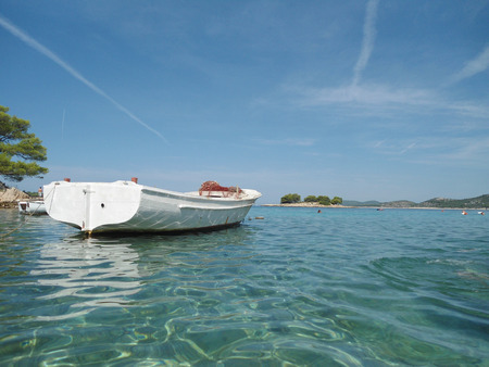 Traditional wooden boat on clear blue water, view from water level photo