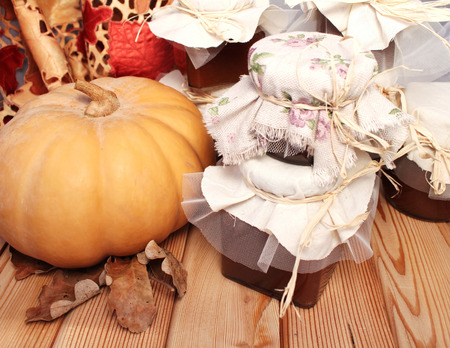 Autumn table, pumpkin, and jam jars on a wooden surface photo