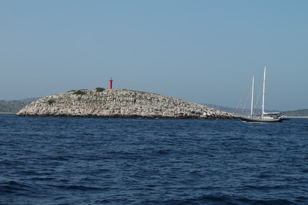 kornati national park: A boat passing in front of a red lighthouse - Kornati National Park (Croatia)