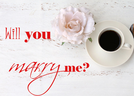 will you marry me: Will you marry me  text on a vintage table a cup of black coffee and a flower