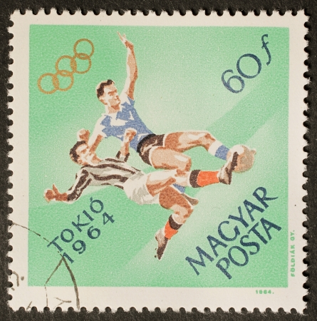 HUNGARY � CIRCA 1964: a stamp printed in Hungary celebrates Olympic games showing illustration of soccer players. Hungary, circa 1964