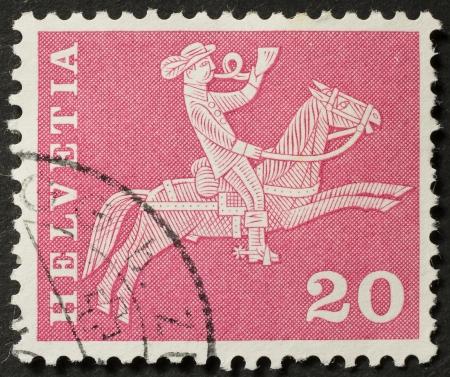 reins: SWITZERLAND � CIRCA 1962  a stamp printed in Switzerland shows illustration of a horseman blowing horn  Switzerland, circa 1962