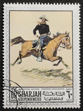 frederic: SHARJAH Emiratos �rabes Unidos alrededor de 1969 un sello impreso en Sharjah Emirate muestra una imagen de un jinete uni�n pintado por Frederic Remington Sharjah, alrededor de 1969