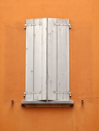 ocher: Old wooden closed window on ocher wall Stock Photo
