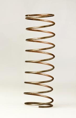 spiraling: Brass spring on white background