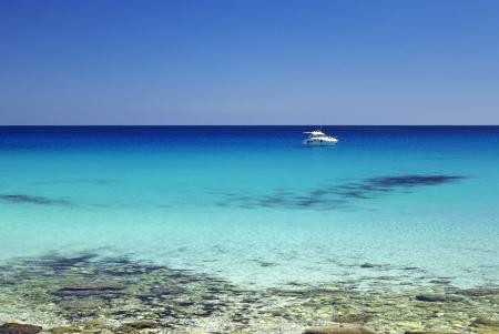 moored: Motorboat anchored not too far from San Vito Lo Capo beach, Sicily