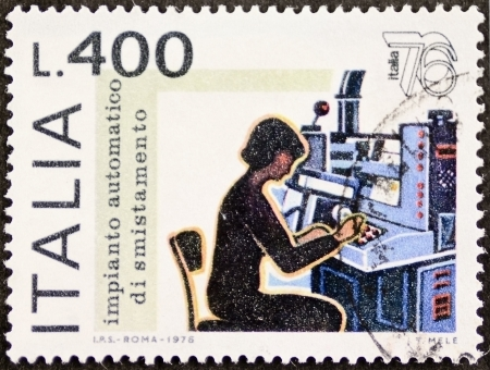 classifying: ITALY CIRCA 1976: a stamp printed in Italy celebrates Expo Italy showing image of a woman working in mail automatic sorting system. Italy, circa 1976 Editorial